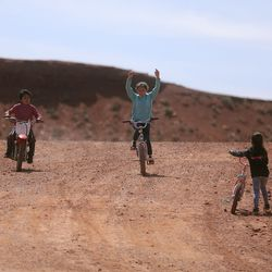 Jarett Hunt, Nesbah Hunt and Sophie Hunt ride on a dirt road near their house in Halchita, San Juan County, which is part of the Navajo Nation, on Friday, April 17, 2020. The Navajo Nation has one of the highest per capita COVID-19 infection rates in the country. The Hunt siblings are asymptomatic but got tested earlier in the day to be safe.