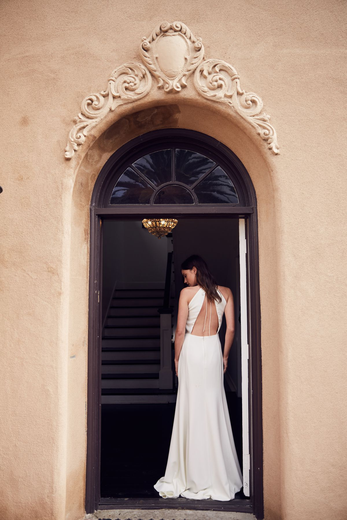 Back of woman and her wedding dress with open back.