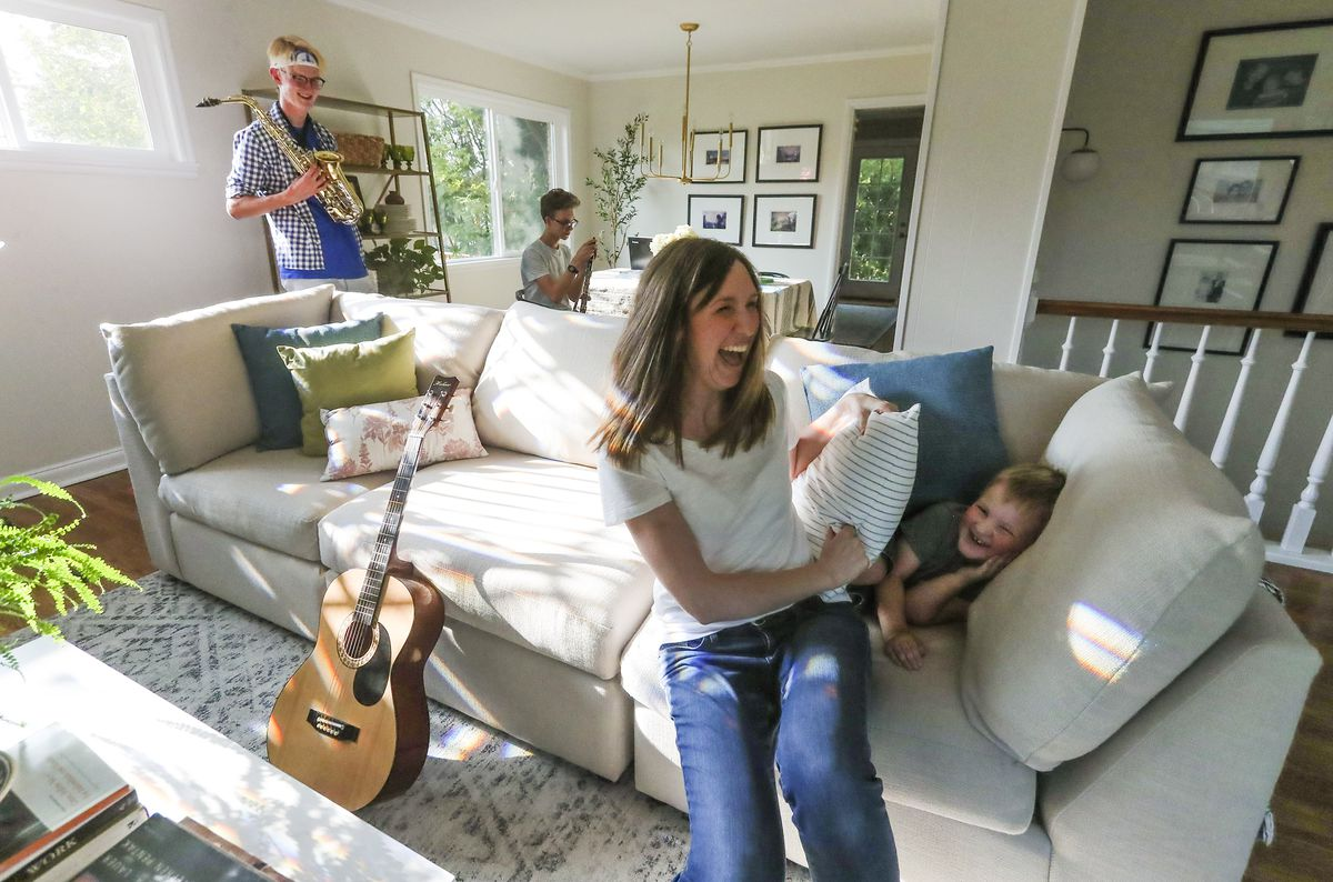 Natalie Larsen laughs with son George as they play hide-and-seek at their home in Salt Lake City on Wednesday, Sept. 16, 2020. Sons CS and Peter are in the background.