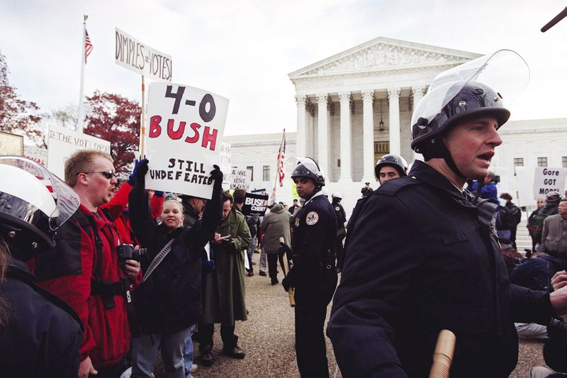 Police officers in black uniforms and helmets stand between crowds of protesters, one side holding pro-Bush signs, and the other holding pro-Gore signs, in front of the Supreme Court building.