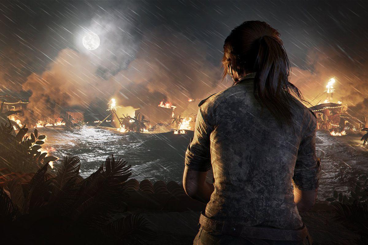 Shadow of the Tomb Raider - Lara sits looking at a burning village