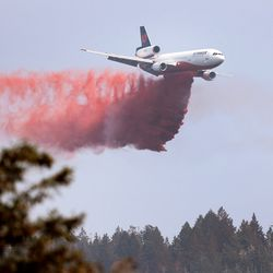 A large tanker begins a retardant drop as crews continue fighting the Parleys Canyon Fire near Park City on Sunday, Aug. 15, 2021.
