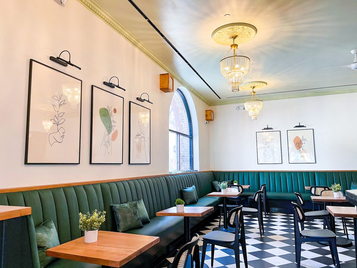The inside of a new restaurant with deep green booths and art on the walls beneath pendant lights.