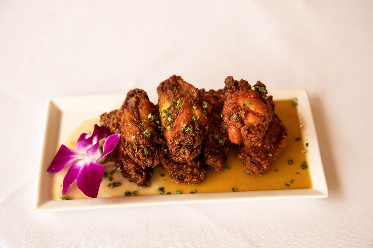 A half dozen crispy chicken wings are arranged on a rectangular white plate on a thin brown sauce. An orchid garnishes the plate.