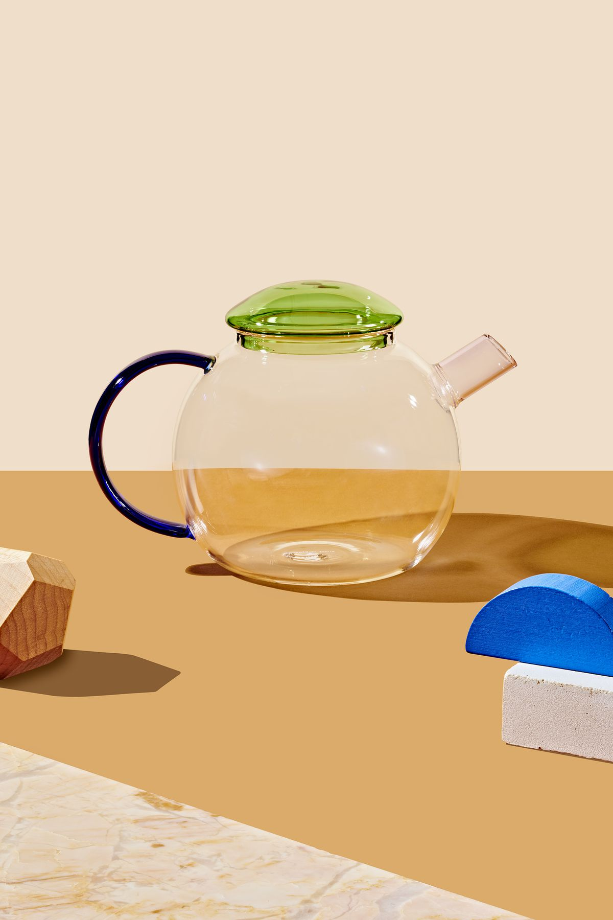 A glass teapot which is part of the 2019 Curbed Holiday Gift Guide. The tea pot has a green lid, blue handle and a pink spout. There are various art objects arranged around the teapot on an orange surface.
