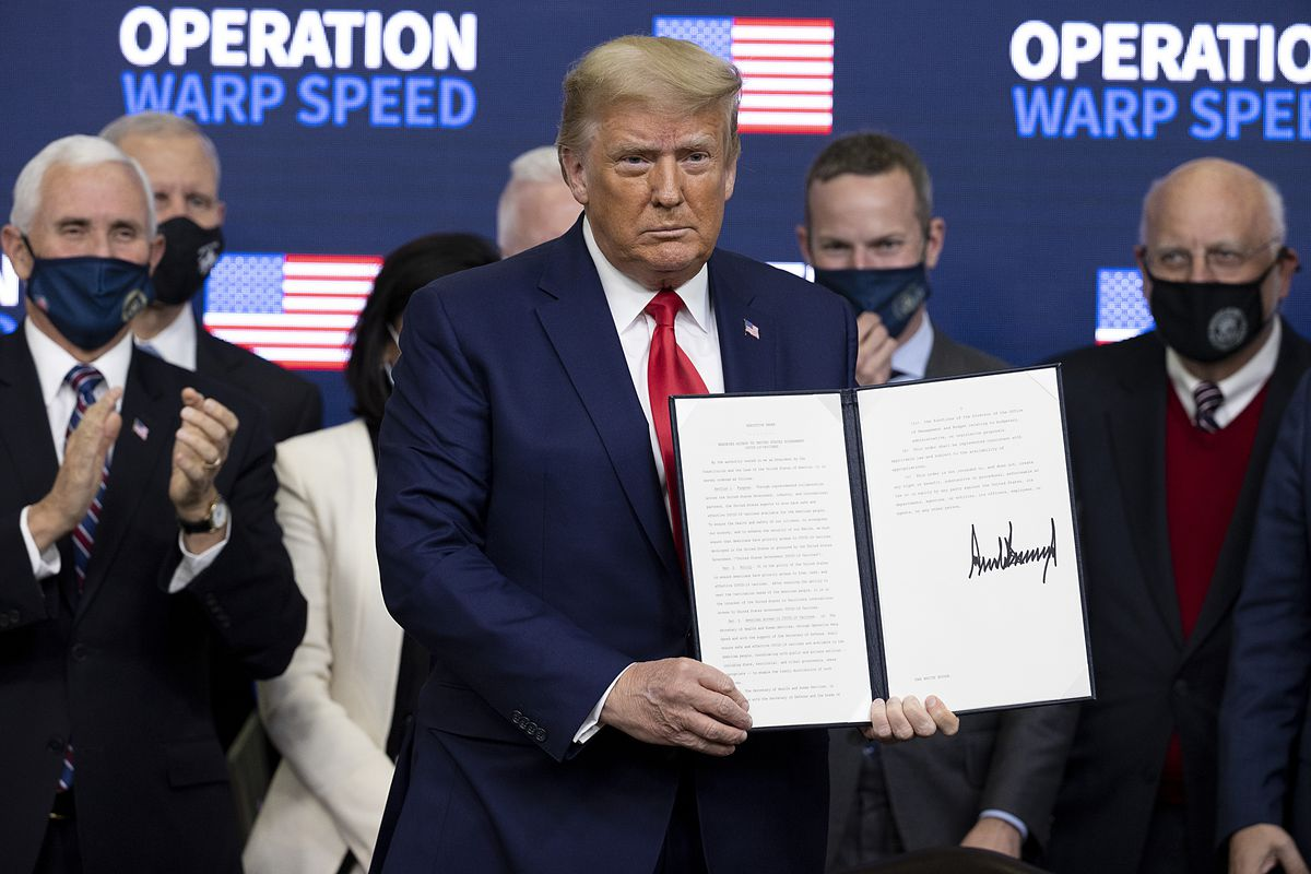 President Donald Trump holds up a signed document while people behind him applaud.