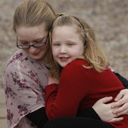 Emma Lewis waits in the arms of a neighbor Ali Jackson for her mother's eagerly awaited return.