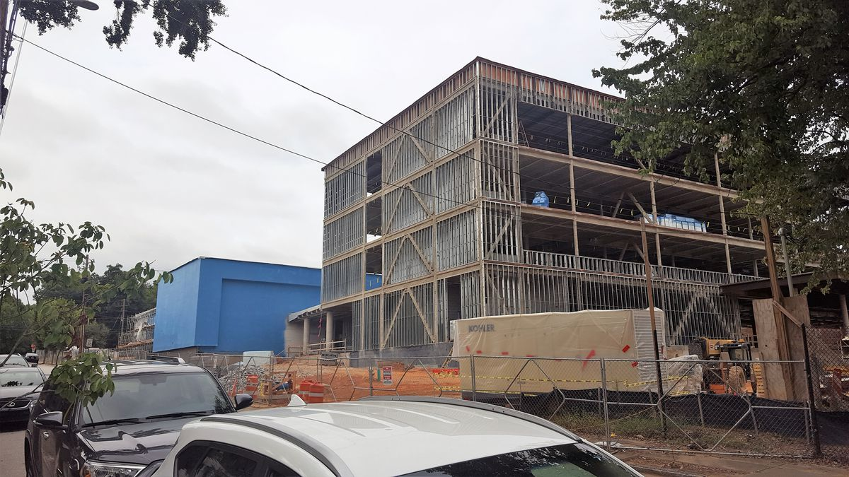 The four-story steel frame stands next to a blue, windowless structure in front of the street.