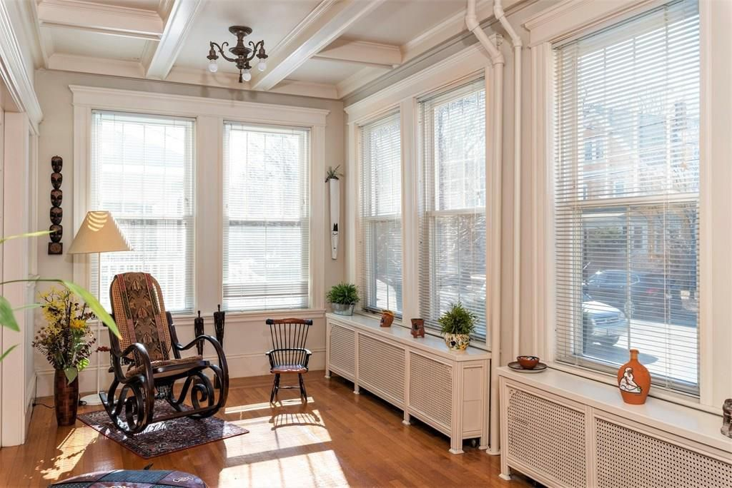 A sunroom with a rocking chair.