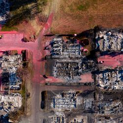 Streaks of red fire retardant dropped by air tankers are seen on Sunday, Sept. 20, 2020, amid structures burned by the Almeda Fire in Talent, Ore.