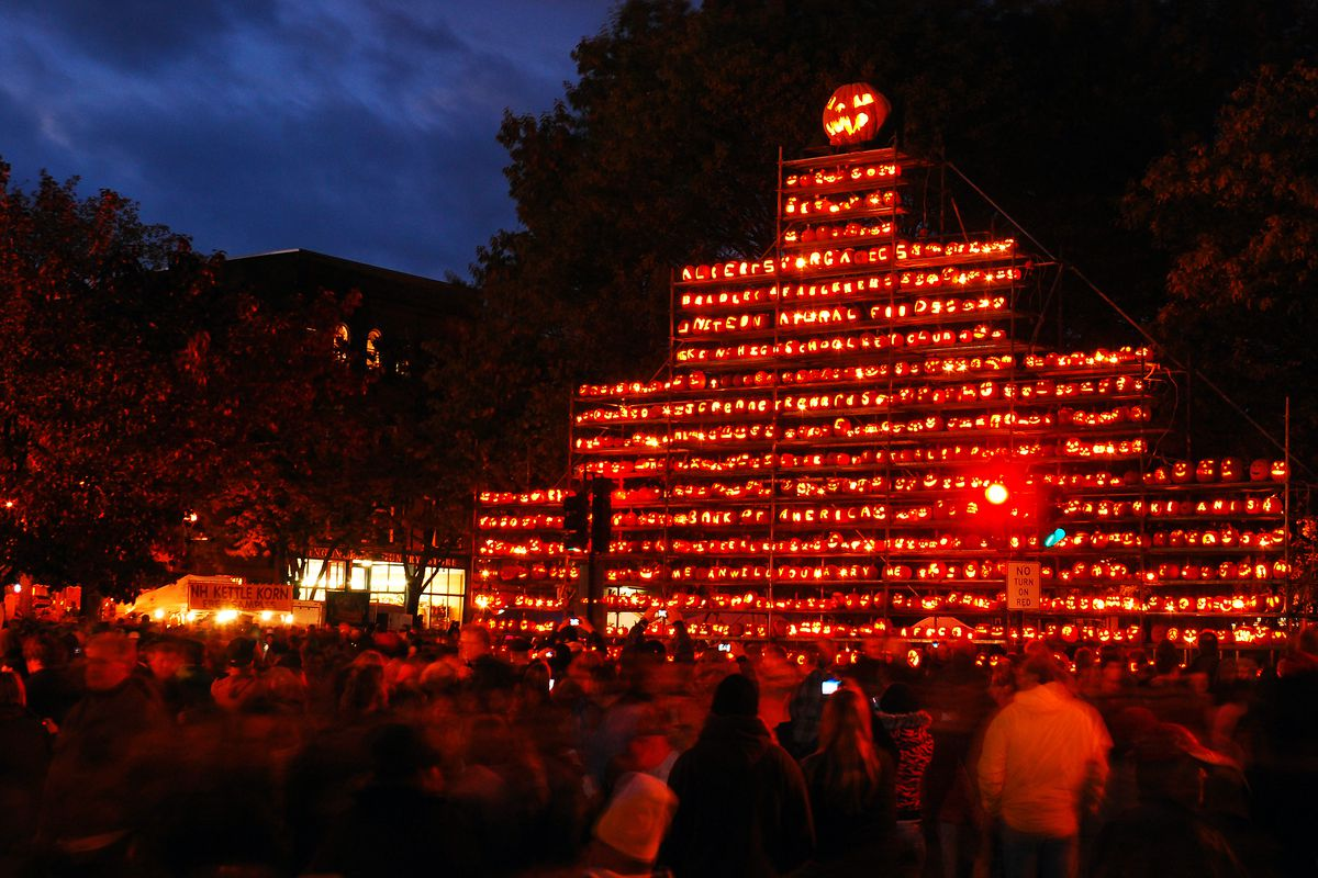 a tower of jack o' lanterns at night.