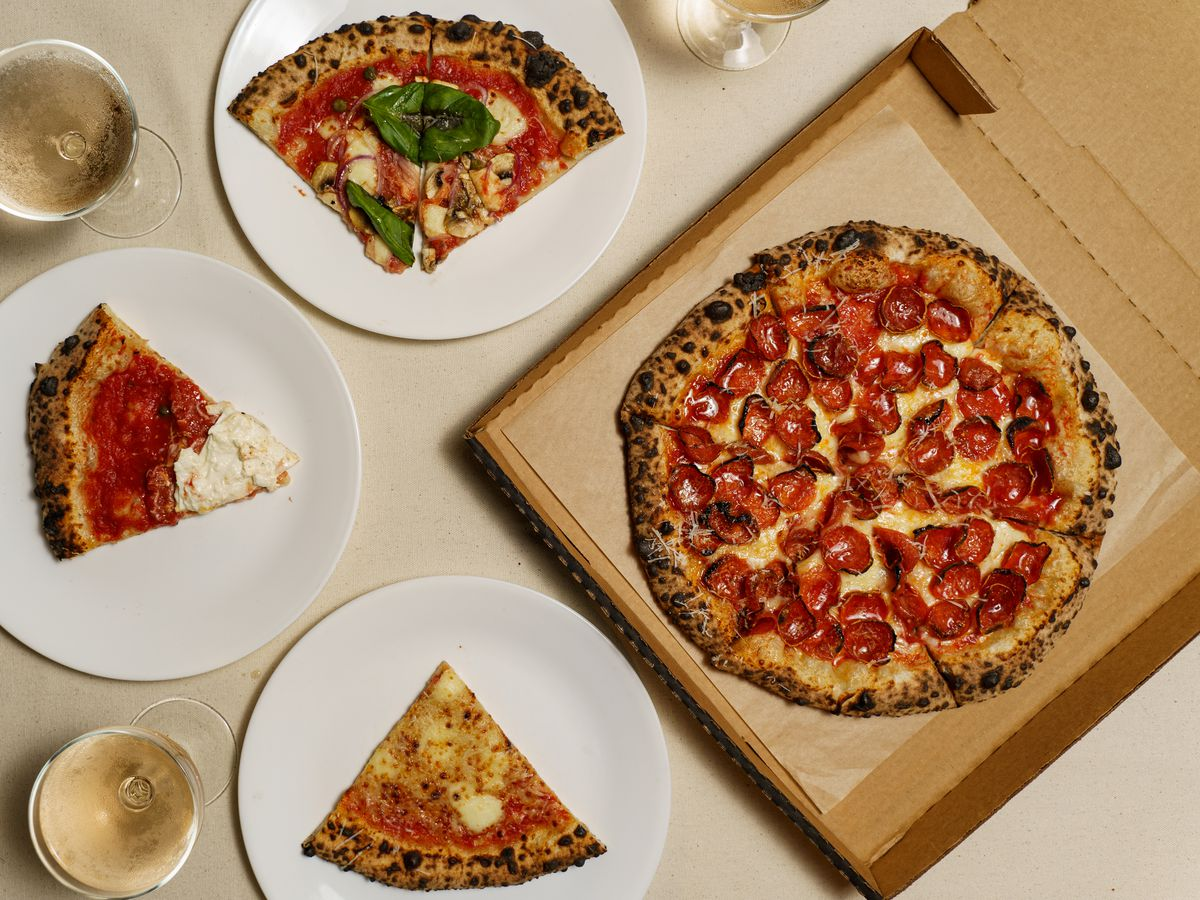 A full pepperoni pizza in a box, and several slices of other types on plates, with coupe glasses of sparkling wine