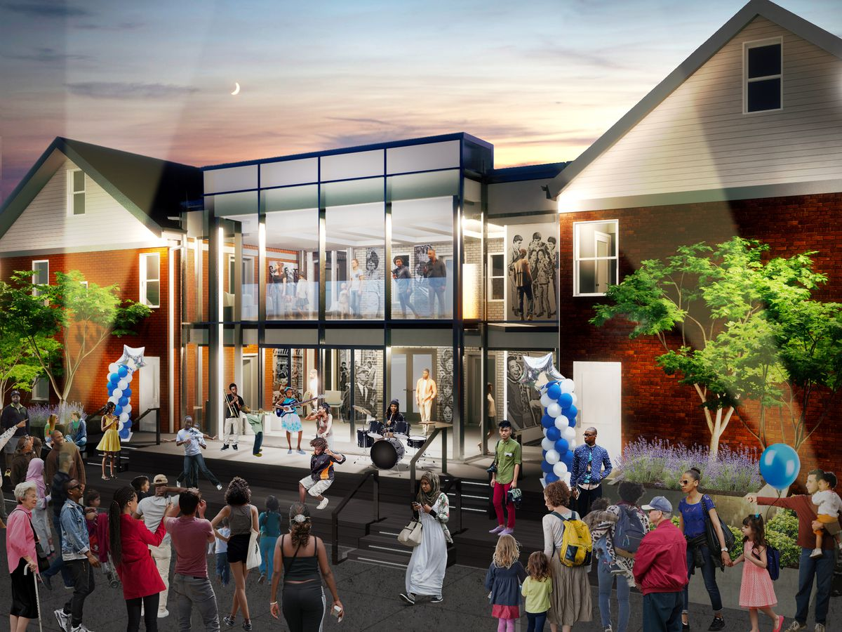 Patrons gather outside as a children's band plays music on an outdoor stage in front of a glass atrium and two brick homes.