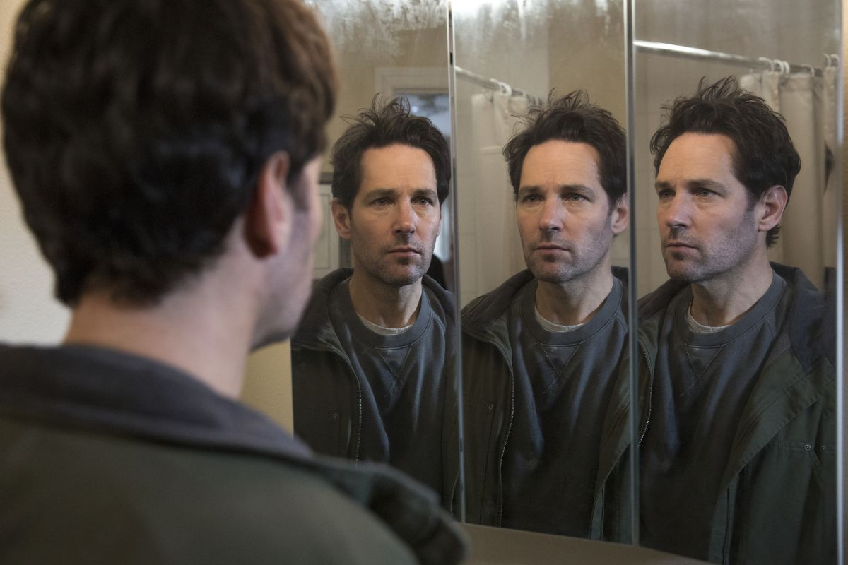 A battered-looking, unsmiling Paul Rudd with mussed hair and hollow eyes examines three mirror reflections of himself from different angles.