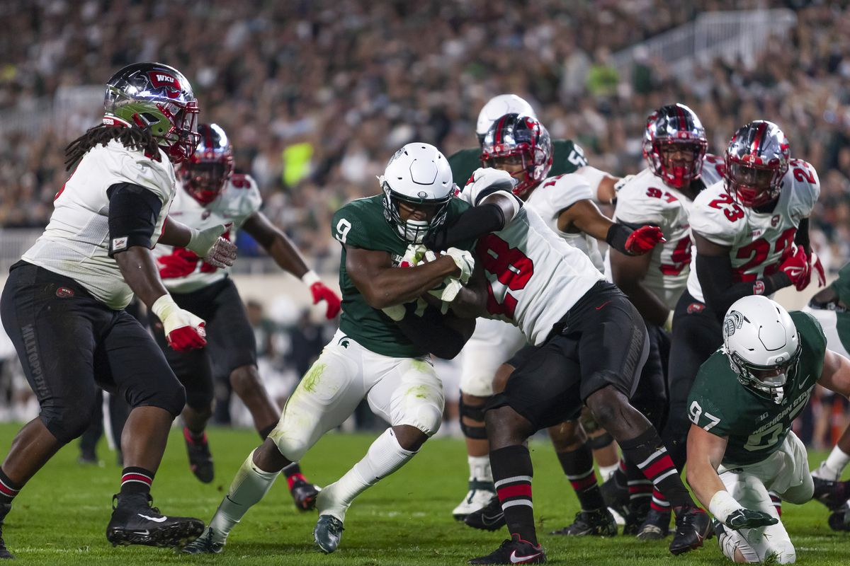 Michigan State Spartans running back Kenneth Walker III (9) runs for a touchdown against Western Kentucky Hilltoppers linebacker Demetrius Cain (28) during the second quarter at Spartan Stadium.