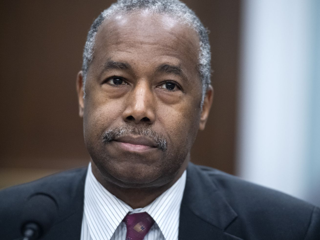Carson, in a dark suit and red tie, frowns slightly.