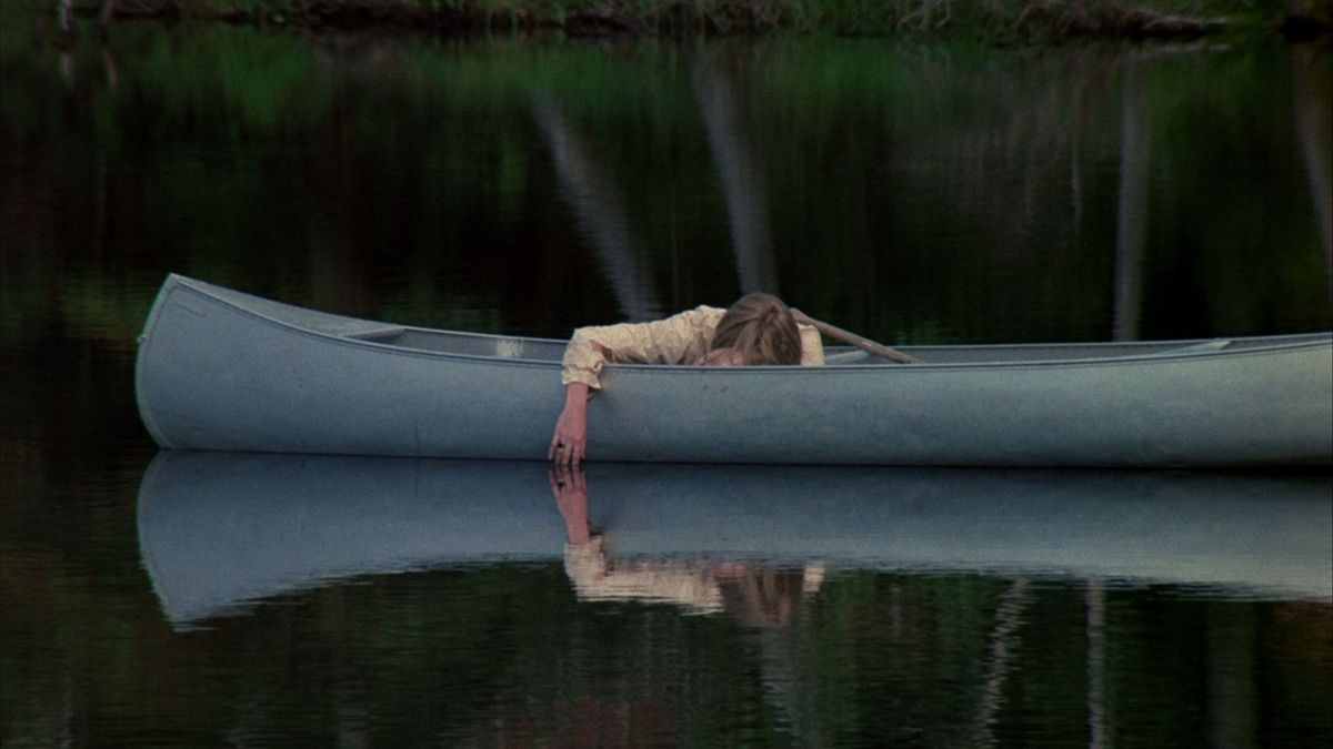 Adrienne King in Friday the 13th lies passed out in a canoe on a lake that reflects her dangling arm.