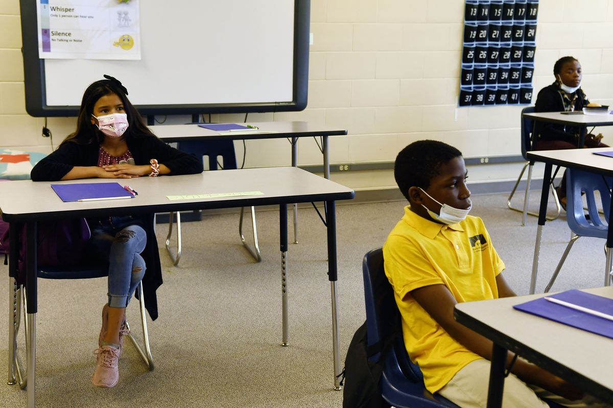 Three middle school students with masks sit at spaced out desks in a classroom, with a white board behind them.