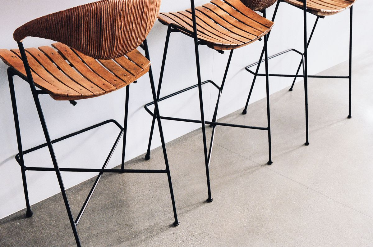 Dark wood and metal bar chairs lined up.