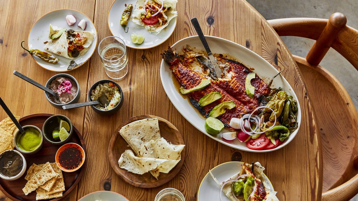 A wood table with several plates of tortillas, sauces, tacos, and a whole roasted fish with wine glasses.