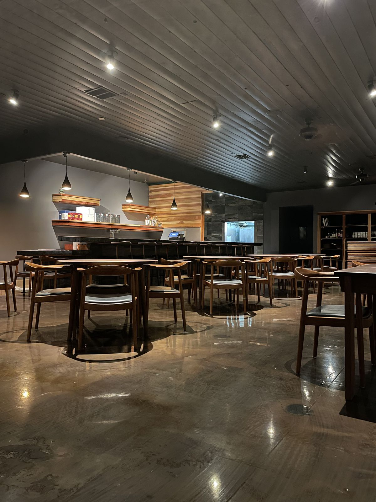 Three tables with dining chairs around them and the bar inside Matsu.