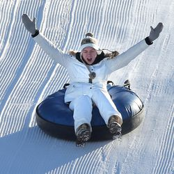 Kaitlyn Lambert raises her hands as she tries extreme tubing down ski jump hills at Utah Olympic Park near Park City Saturday, Dec. 26, 2015, in Synderville Basin.