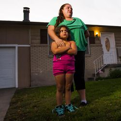 Kristen Morales, standing with her daughter, Sophia, 6, gets emotional as she describes her relationship with one of the victims of a triple homicide, Heike Poike, at 639 N. Sir Philip Drive in Salt Lake City on Saturday, Sept. 19, 2015.