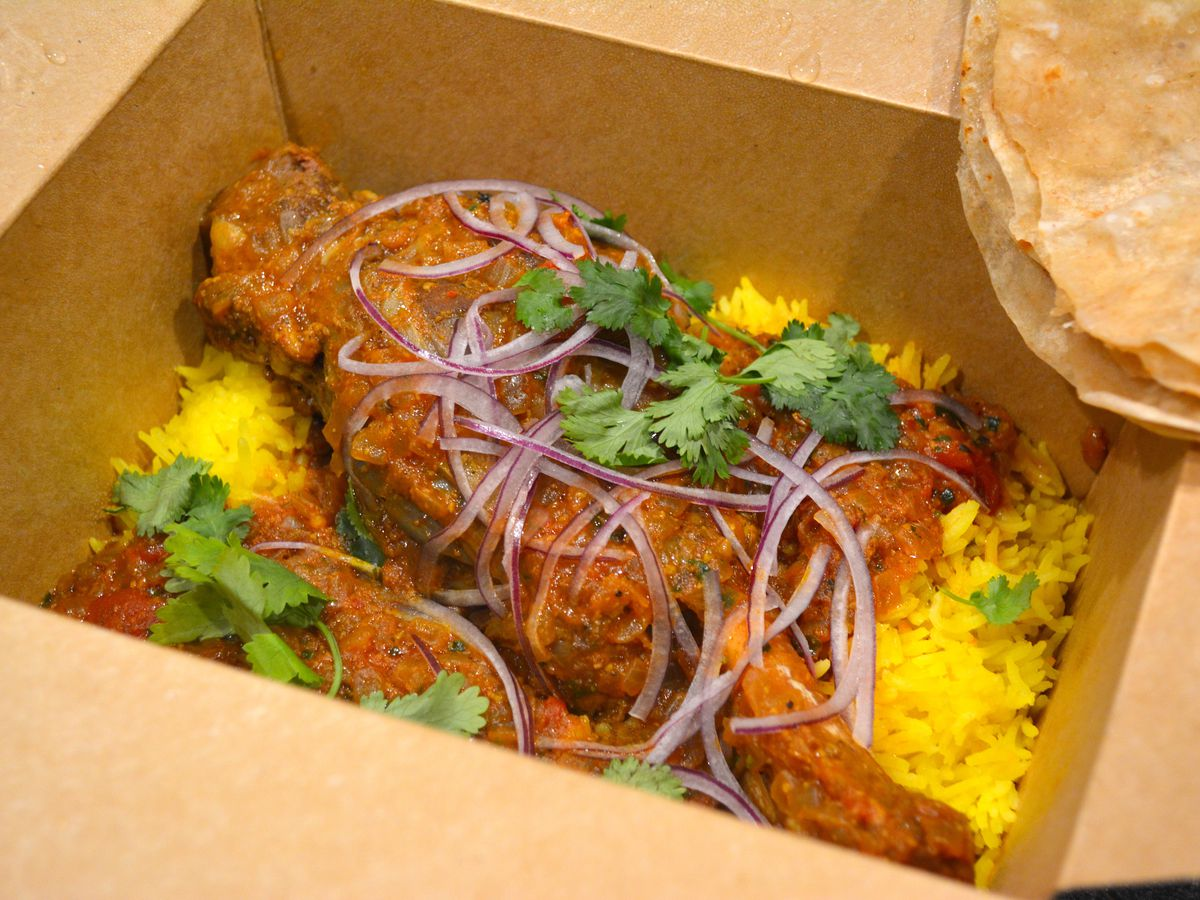 Indian-style lamb shank over rice in takeout container