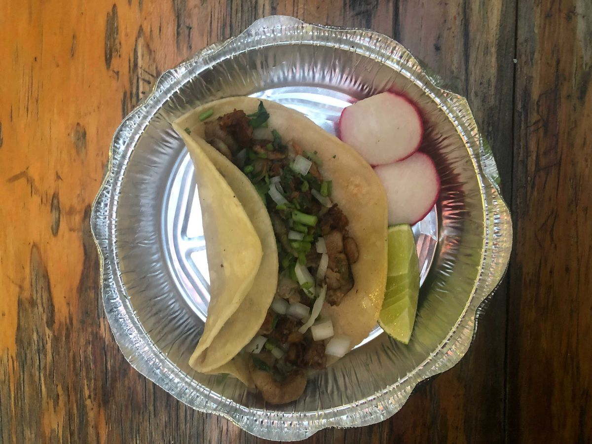A foil container with a taco filled with brown meat inside, with a lime wedge and two radish slices off the side. The container sits on a brown wooden table.