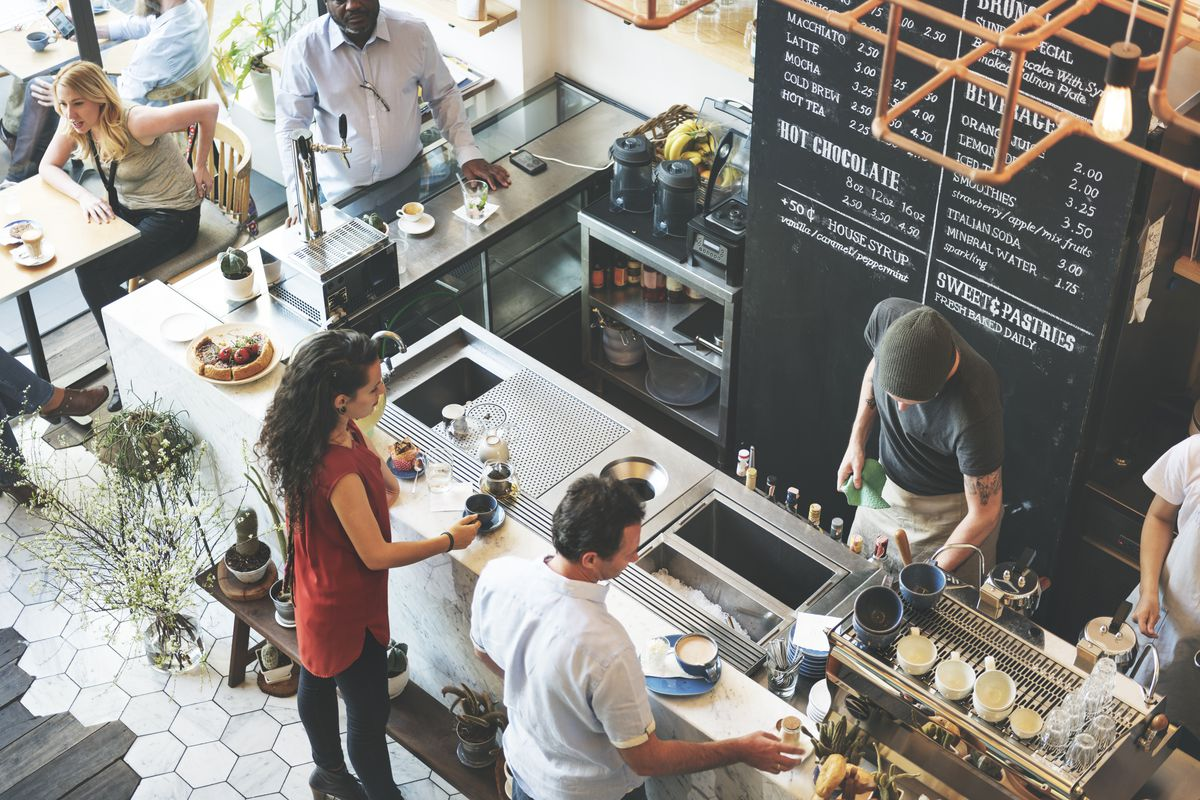 A man takes an order behind a counter in an overhead shot of a cafe