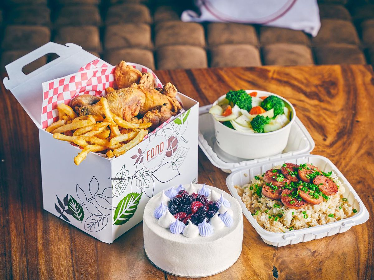Takeout containers on a wood table, including a large bucket of fried chicken, a small cake, a vegetable rice dish, and steamed veggies
