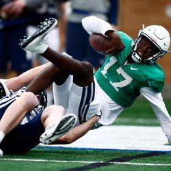 BYU quarterback Stacy Conner is tackled during the Cougars' practice in the Indoor Practice Facility on Thursday, March 15, 2018, in Provo.