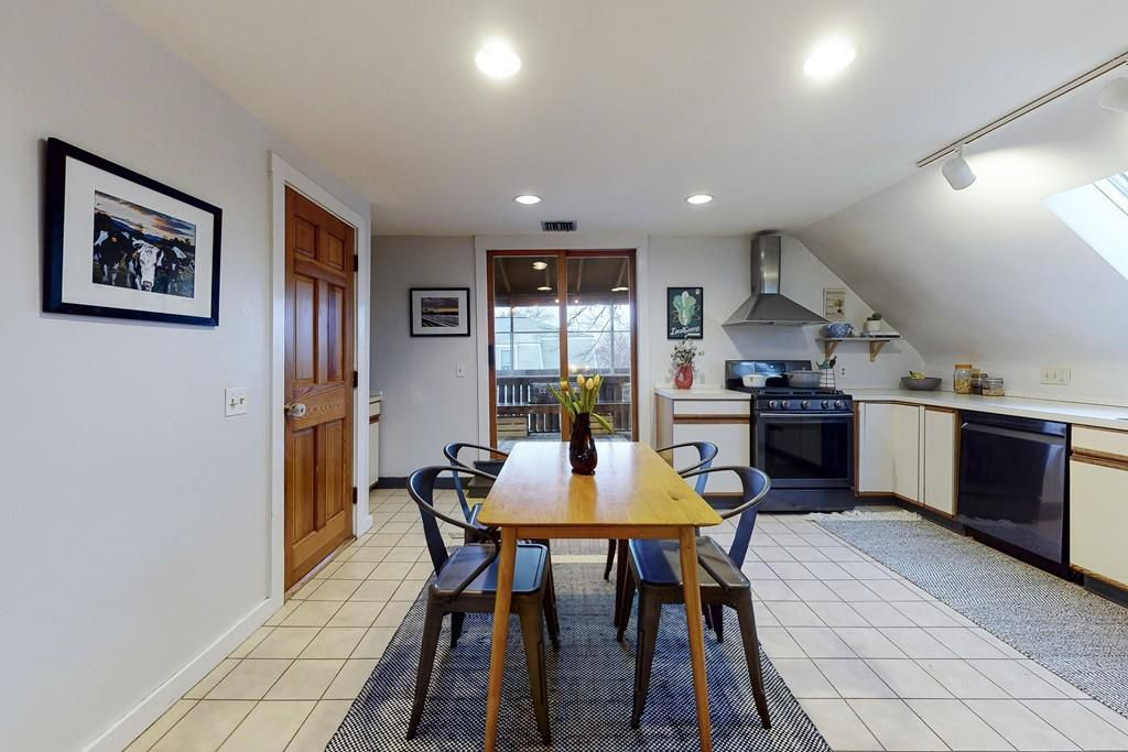 A spacious kitchen with an L-shaped counter and a table and chairs.