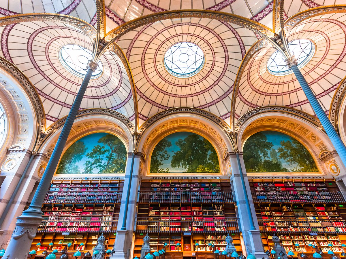 The interior of the Bibliotheque Nationale de France. There are many shelves full of books. The ceiling is ornately decorated and glass.