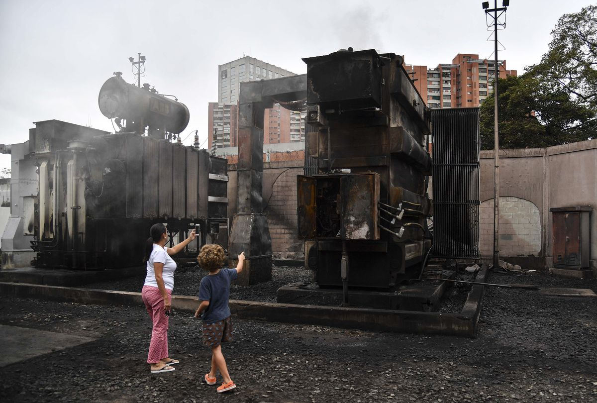 A woman and a child take pictures of a damaged power substation of state-owned electricity company Corpoelec in Caracas where explosions of unknown cause took place early on March 11, 2019.