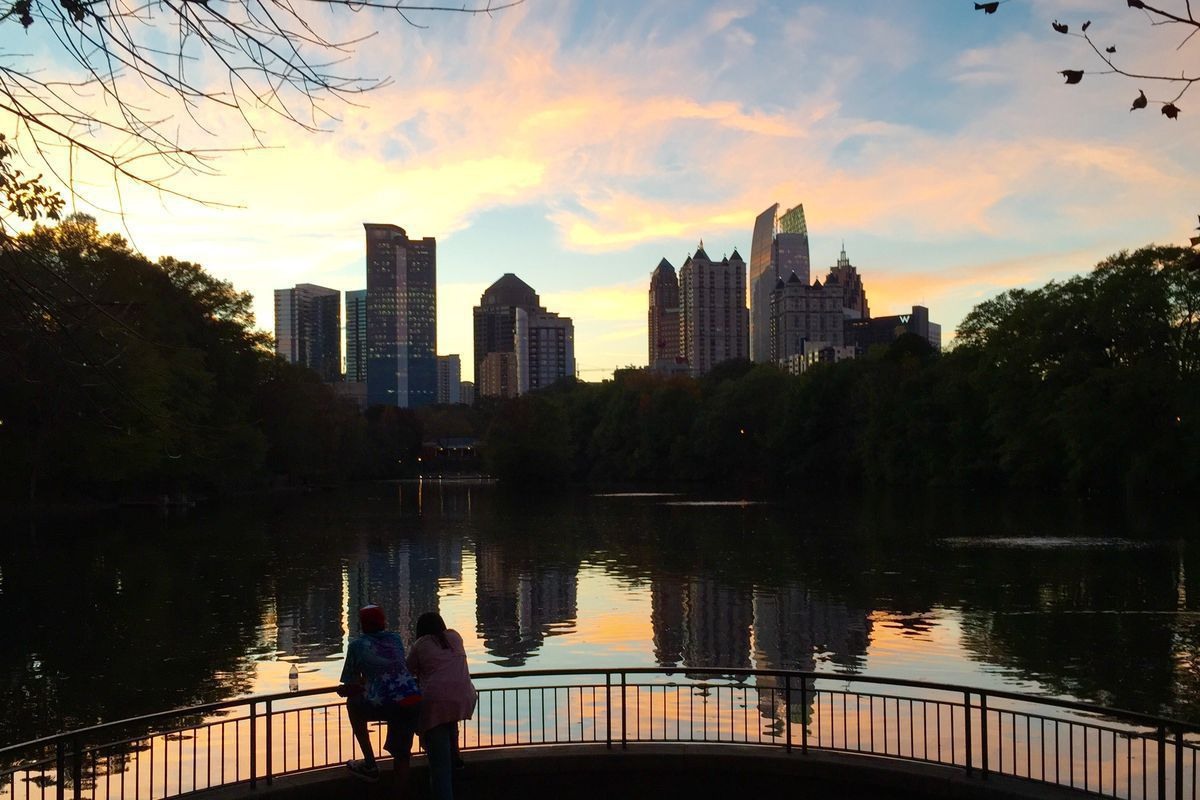 A view of Piedmont Park's Lake Clara Meer at sunset on the water, with two people in the foreground.