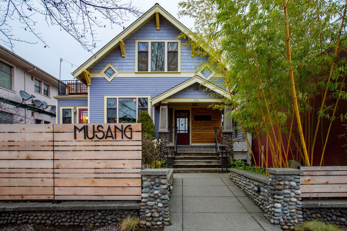 The light purple exterior of Musang's Craftsman home, with the name of the restaurant on a wood fence outside.