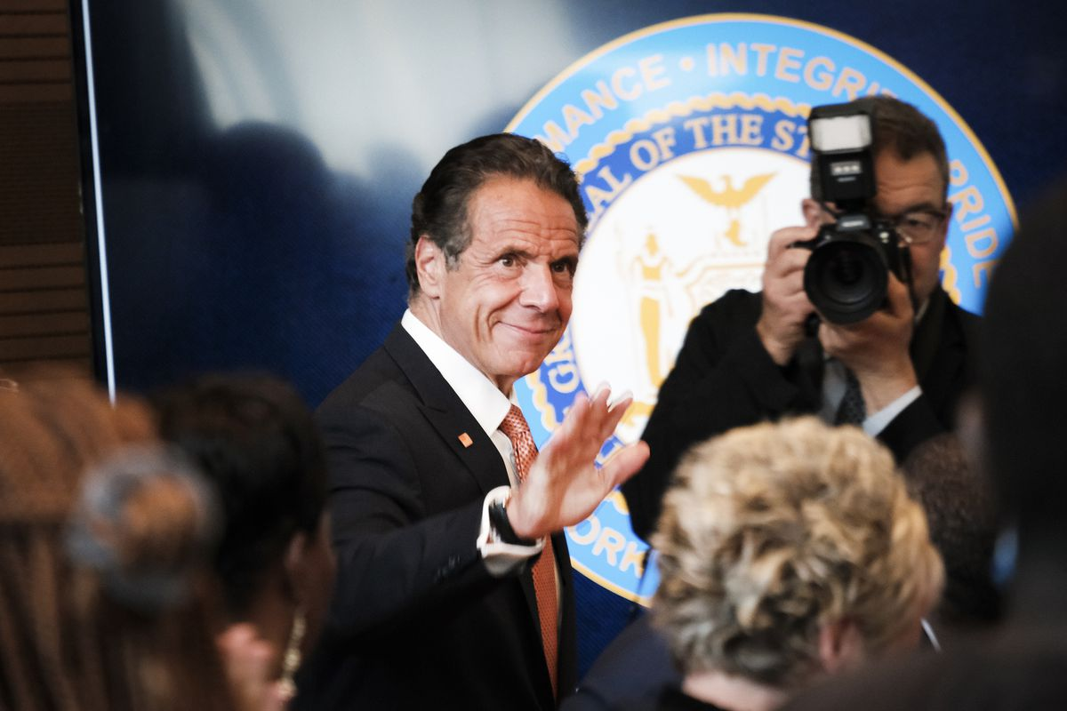 New York Gov. Andrew Cuomo waves to members of the press at a press conference.