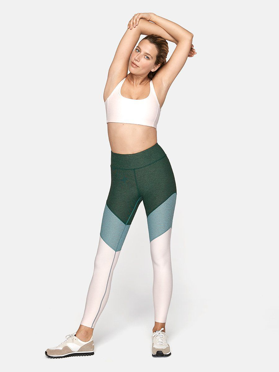 A model wears green, teal, and white colorblocked leggings.