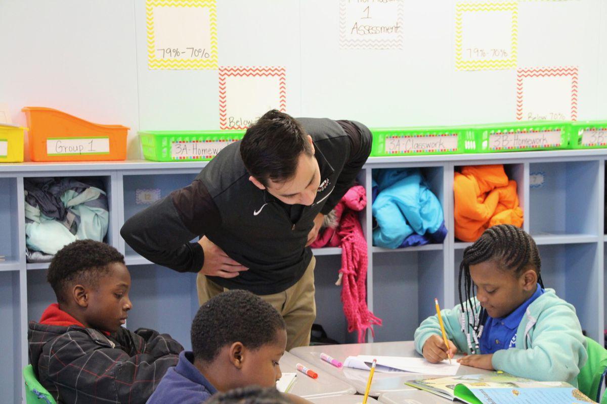 David Makita checks on students' work while visiting a classroom.
