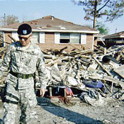 A Guardsman stands in front of the rubble that was Dion Harris' home.