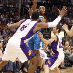 New Orleans Hornets guard Jarrett Jack, center, passes the ball as he is hemmed in along the sideline by Phoenix Suns forward Channing Frye, left, and guard Steve Nash, right, in the first quarter of an NBA basketball game Sunday, April 1, 2012, in Phoenix.
