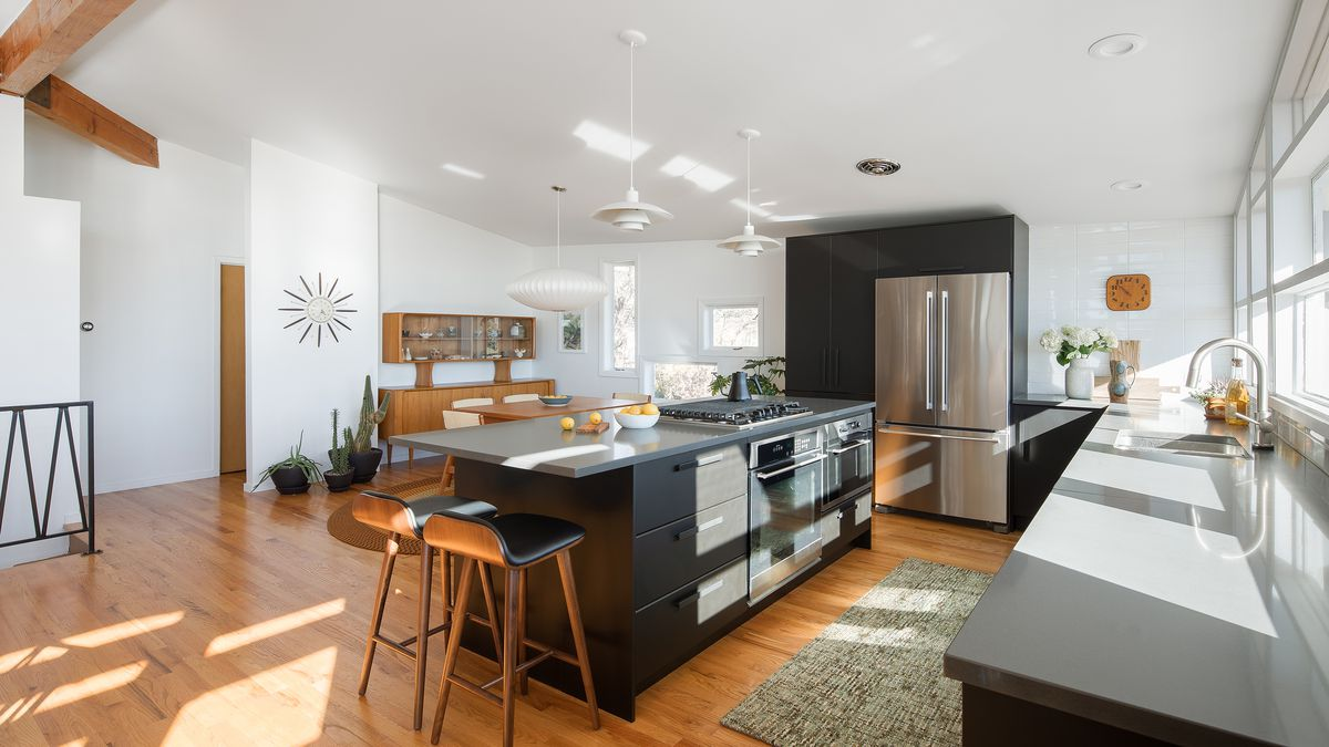 A kitchen with a black kitchen island. The countertops are light grey and the cabinetry is black. There are stools next to the kitchen island. The floor is hardwood and there is a grey area rug,