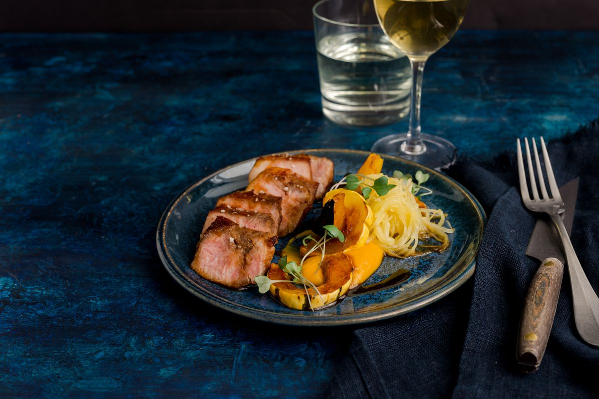 A pork dish with a side of squash and a glass of wine
