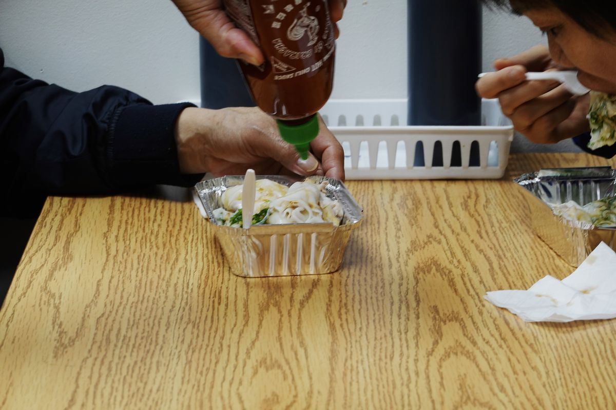 A customer squeezes a bottle of Sriracha into a container of rice rolls, as another customer takes a bite of their rice roll