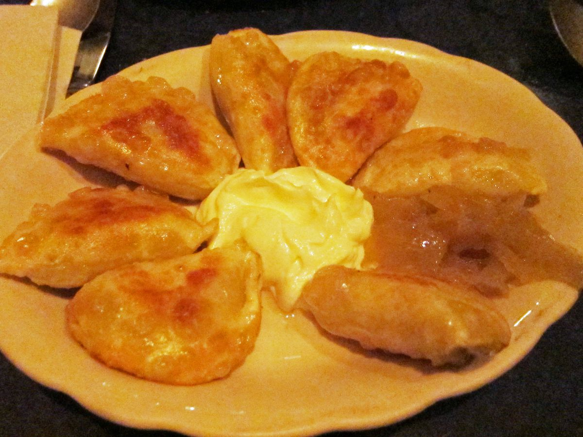 A circle of cheese pierogi with sour cream in the middle.