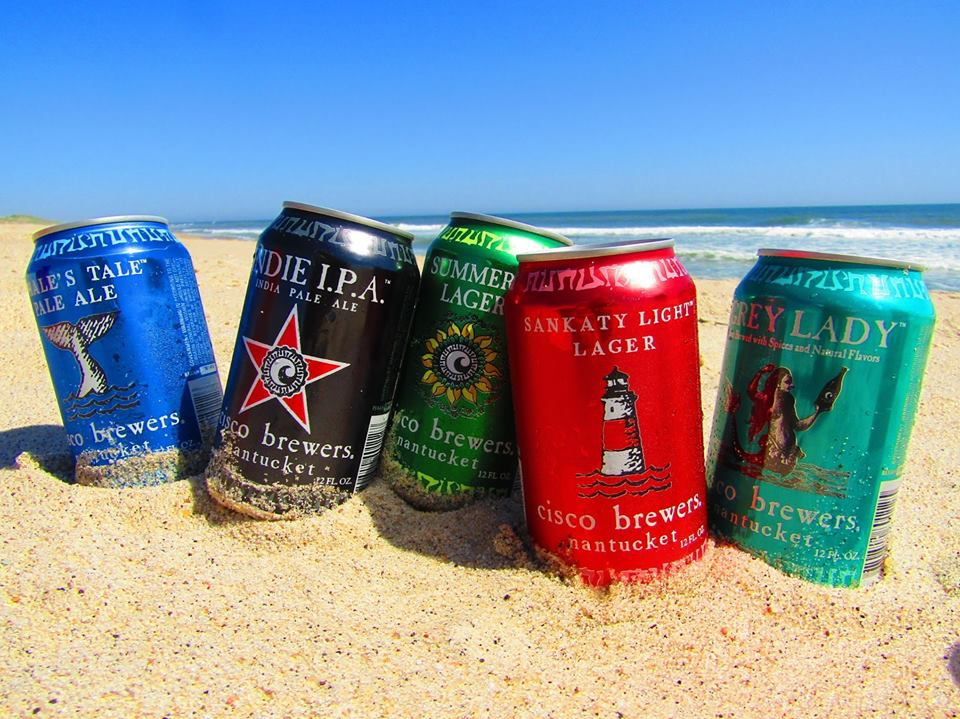 A lineup of Cisco Brewers beer cans stand on the sand of a beach with water visible in the background