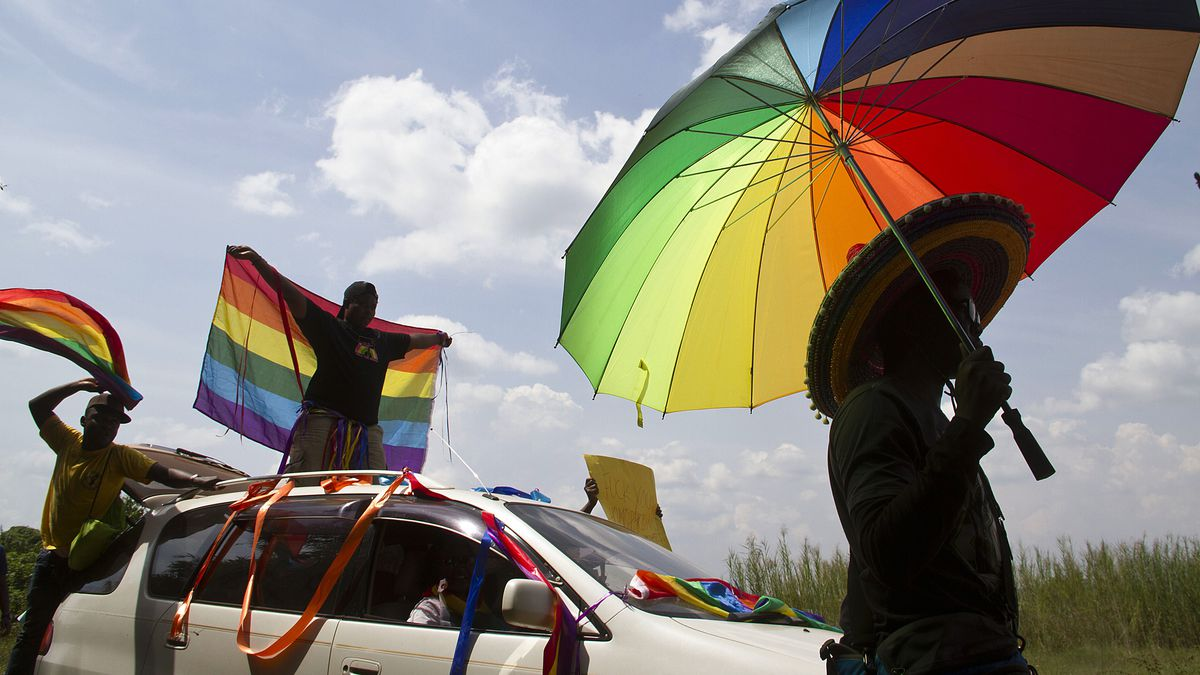 A person holds an umbrella bearing the colors of the rainbow flag as others wave flags during the the first gay pride rally since the overturning of a tough anti-homosexuality law in Entebbe, on August 9, 2014.