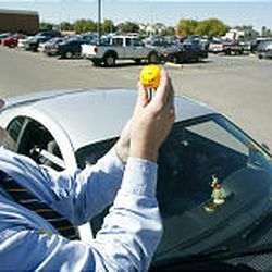 """Mike Mower places a ball that says """"Provo Gives Kids a Brake!"""" on a Provo High student's car antenna."""