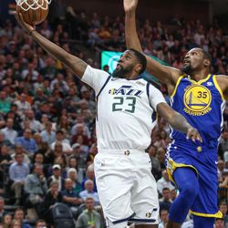 Utah Jazz forward Royce O'Neale (23) goes to the hoop ahead of Golden State Warriors forward Kevin Durant (35) during the game at Vivint Arena in Salt Lake City on Tuesday, April 10, 2018.